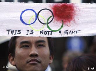 An activist protests holding a banner with a circle of what looks like blood making the red Olympic ring