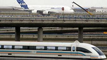 ** ARCHIV ** Ein Transrapid faehrt am 25. November 2006 in Shanghai an einem Airbus A380 vorbei. Bundesregierung, bayerische Landesregierung und Industrie haben beschlossen, die Transrapid-Strecke vom Muenchener Hauptbahnhof zum Flughafen nicht zu bauen. Das verlautet am Donnerstag, 27. Maerz 2008, nach einer Krisensitzung im Berliner Bundesverkehrsministerium aus Regierungskreisen. (AP Photo/Color China Photo) ----** FILE ** A maglev train runs past as a new Airbus A380 sits on the tarmac at Shanghai Pudong International Airport Friday Nov. 24, 2006 in Shanghai, China. The Airbus A380 superjumbo flew home Friday after stopovers in three of China's biggest cities, visits symbolizing the company's ambitions in the booming Chinese market, where the outlook for the colossal jet is mixed. (AP Photo/Color China Photo) ** CHINA OUT **