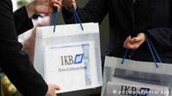 A bag with the IKB logo passes from one person to another