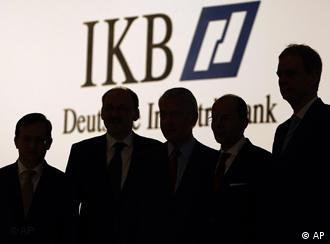 Five people silhouetted in front of an IKB sign
