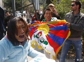 Police surround a pro-Tibet protesters, detained outside the marble Panathenian Stadium where the Olympic flame handover ceremony was held for the Beijing Olympics, in Athens on Sunday, March 30, 2008.