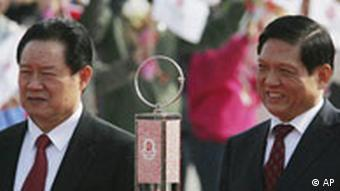 Liu Qi, the president of the Beijing Olympics organizing committee (BOCOG), right, and Politburo Standing Committee member Zhou Yongkang stand behind the Olympic flame on its arrival in China, at Beijing airport Monday March 31, 2008. (AP Photo/Greg Baker)