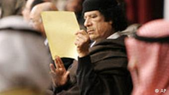 Libyan leader Moammar Gadhafi, center, reads a paper during the closing session of the Arab Summit in Damascus, Syria, Sunday March 30, 2008. Iraq is refusing to endorse the final statement from the Arab summit in Syria because it does not condemn terrorism in the war torn country.(AP Photo/Hussein Malla)
