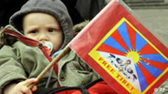 A one year old boy Jano hold a Tibet flag during a vigil to commemorate the victims of the crack down of unrests in Tibet by Chinese security forces in Frankfurt, Germany, Monday, March 31, 2008