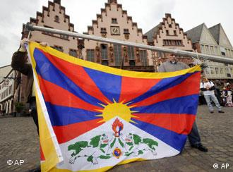 Three protestors holding Tibetan flag in a market square