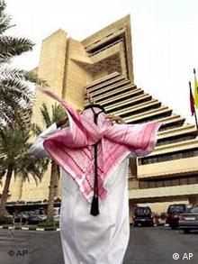 A Qatari official in Arabic dress walks towards Doha Sheraton Hotel, which is the main venue for the World Trade Organisation (WTO) meeting in Doha, Qatar, Tuesday Nov. 6, 2001. Ministers of 142 different countries will meet in Doha from Nov. 9-13 for the WTO ministerial meeting. (AP Photo/Kamran Jebreili)
