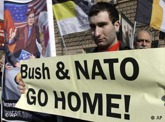 Protestor holding banner reading Bush & NATO go home!