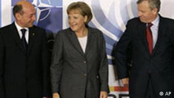NATO Secretary-General Jaap de Hoop Scheffer right, and Romanian President Traian Basescu, left, German Chancellor Angela Merkel during an official arrival ceremony for NATO leaders at the Cotroceni Presidential Palace in Bucharest, Wednesday April 2, 2008, before a working dinner which preceded the start of the NATO Summit conference.