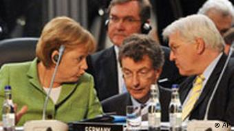 Merkel and Steinmeier speaking to each other at a conference