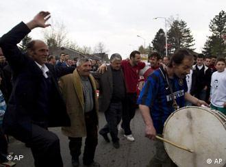 Kosovars dance in the main street of Decane