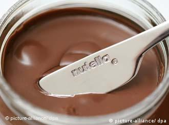 knife dipping into a jar of Nutella