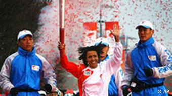 Olympic champion Kelly Holmes runs with the Olympic torch held aloft after completing the final leg of the Olympic Torch Relay at the O2 Arena, formerly known as the Millennium Dome, in east London