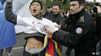 A protestor is detained by a police officer during the Olympic torch relay in Paris, on Monday, April 7