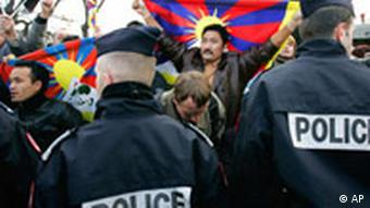 Police officers restrain pro-Tibet demonstrators, waving a Tibetan flag, during the Olympic torch parade shortly after its beginning near the Eiffel tower
