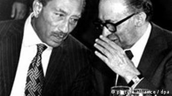 Israeli Premier Menachem Begin whispers in Anwar Sadat's ear