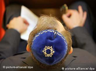 A view of the top of a man's head sitting in a Berlin synagogue