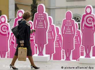 A woman passes an exhibition of pink dolls in front the Portuguese Parliament in Lisbon