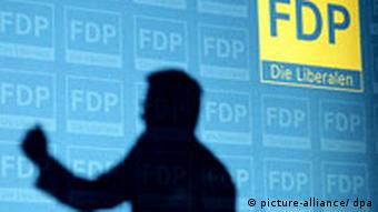 Silhouette of party leader Guido Westerwelle in front of FDP logo