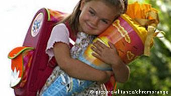 Kleines Mädchen am ersten Schultag umarmt ihre Schultüte (Foto: picture-alliance)