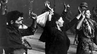 گروهی از زنان و مردان حین ویرانسازی گتوی ورشو توسط نیروهای اس اس در آوریل و مه ۱۹۴۳ دستهای خود را به نشان تسلیم بالا نگاه میدارند