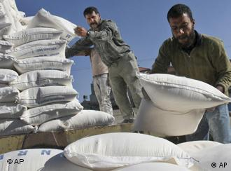 workers carry flour bags at a United Nations food aid distribution center