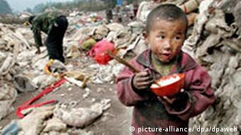 A young boy in a trash heap eats rice from a boy