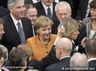 German Chancellor Angela Merkel and colleagues waiting to cast their ballots in the vote on the Treaty of Lisbon in the German Bundestag