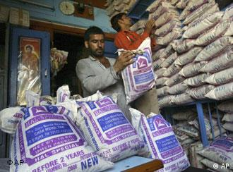 A shopkeeper arranges rice bags in Jammu, India, Thursday, April 24, 2008. India's federal government is planning to take several steps, including banning the exports of some commodities, to control the rising prices of food, cement and steel, the finance minister said Tuesday. India's key inflation rate surged to a 3-year high of 7.41 percent last month, before dropping to 7.14 percent for the week that ended April 5, according to government data.(AP Photo/Channi Anand)
