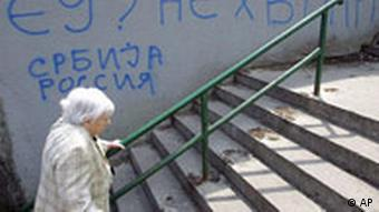 A woman walks past graffiti on a wall reading, EU (European Union)? No, thanks.