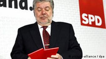 Kurt Beck standing in front of an SPD poster