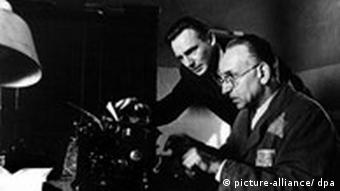 Liam Neeson and Ben Kingsley at a typewriter in a scene from the Spielberg film Schindler's List