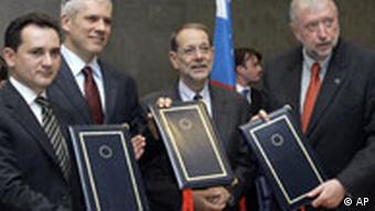 Serbian Deputy Prime Minister Bozidar Djelic, Serbian President Boris Tadic, EU foreign policy chief Javier Solana, and Slovenian Foreign Minister Dimitrij Rupel hold documents after signing an EU-Serbia accord