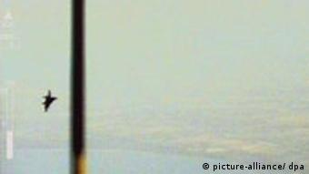 a still from a video showing a military plane in the distance