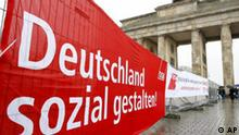 Ein Plakat haengt am Donnerstag, 1. Mai 2008, in Berlin waehrend einer Maikundgebung des Deutschen Gewerkschaftsbundes vor dem Brandenburger Tor an einem Zaun.