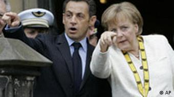 Nicolas Sarkozy and Angela Merkel stand pointing their fingers out in front of them