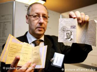 Gerrit Jan Evers holds up documents from the Nazi archive