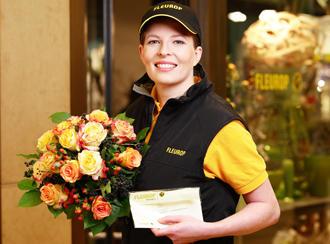 Eine Frau in Uniform hält einen Strauß Blumen