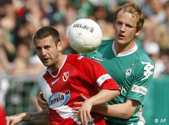 Cottbus' Timo Rost, left, and Bremen's Petri Pasanen, right, challenge for the ball