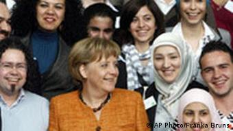 Merkel with young women, some in headscarves