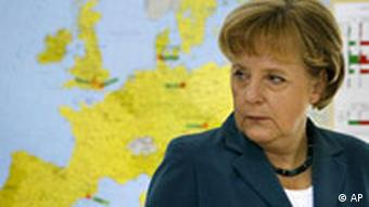 Germany's Chancellor Angela Merkel stands in front of an European map