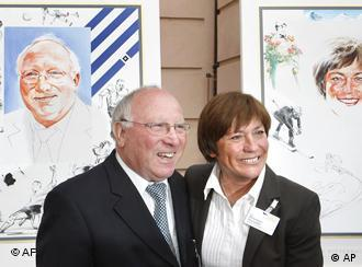 Former soccer player Uwe Seeler, left, and former ski racer Rosi Mittermaier, right, pose in front of their portraits prior to the opening of the exhibition Hall Of Fame Of German Sports in Berlin