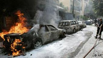 A fire fighter tries to extinguish burning cars during clashes between opposition supporters and the Lebanese army in Beirut, Lebanon