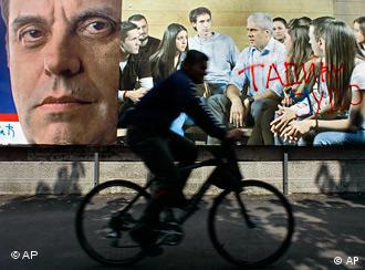 A man on bicycle drives by a pre-election billboards showing Serbia's nationalist prime minister Vojislav Kostunica,left, and pro-western President Boris Tadic with graffiti reading Tadic, Judas, in downtown Belgrade
