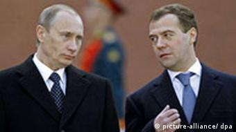 Russian President Dmitry Medvedev speaks with his predecessor Vladimir Putin