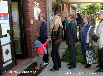 People wait to vote in front of the poling station, for the parliamentary elections in Belgrade, Serbia