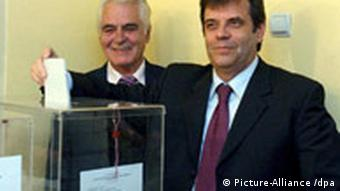 Serbia's Prime Minister, Vojislav Kostunica (R), casts his ballot for the parliamentary elections