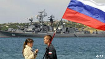Ein Russe mit russischer Flagge in der Hand steht gegenüber einem Mädchen in Marine-Paradeuniform in der russischen Basis Sevastopol in der Ukraine (Foto: AP)