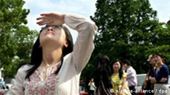 A girl looks up at the shaky high-risers in Hangzhou in east China's Zhejiang province