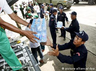 Burmese soldiers unload water bottles from the first US aid plane