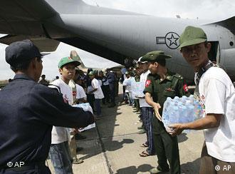 Soldiers from Burma unload water from a US Air Force plane